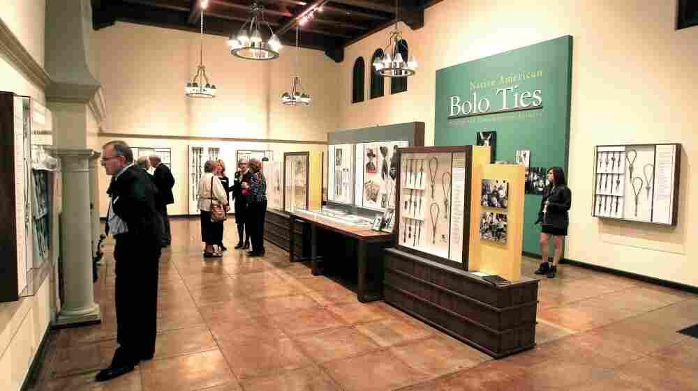 Patrons examine the bolo ties exhibit at the Heard Museum in Phoenix.