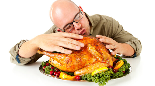 A man embracing a turkey.