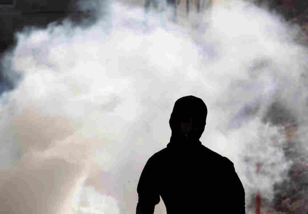 Anti-government protester runs away from tear gas fired by riot police Wednesday in A'ali, Bahrain.