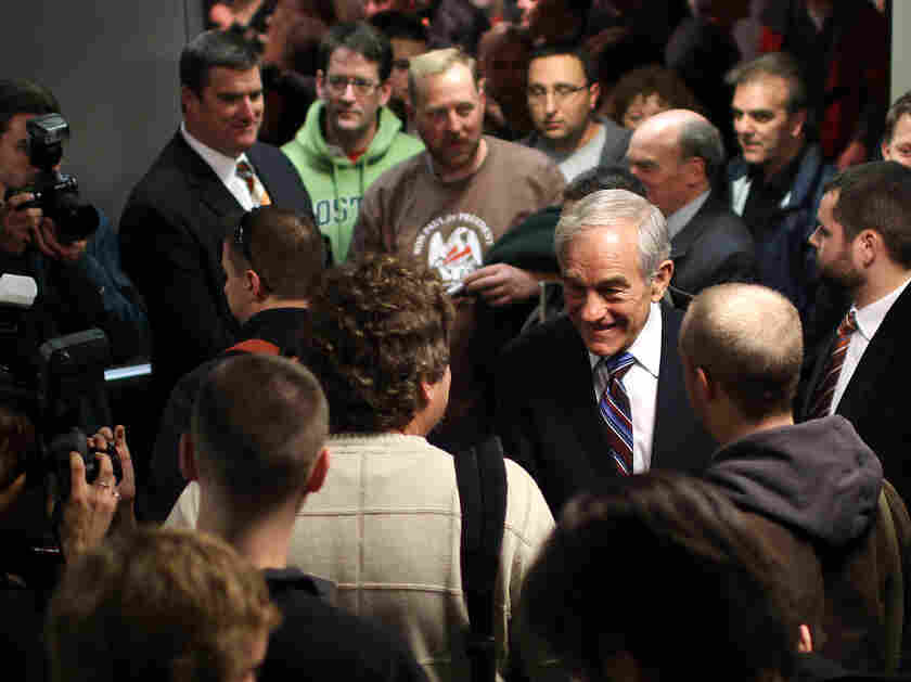 Republican presidential candidate Rep. Ron Paul of Texas is surrounded by supporters after speaking at a town hall meeting in Keene, N.H., on Monday.