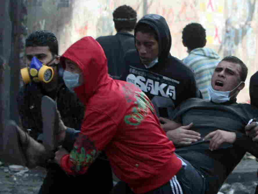 Egyptian protesters carried away a man suffering from tear gas during clashes with riot police earlier today near Tahrir Square, in Cairo.