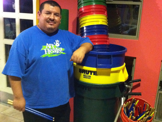 Mario Barela stands next to the supplies he uses for his percussion class. He teaches the fundamentals of drumming to children in a Phoenix domestic violence shelter. (NPR)