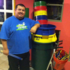 Mario Barela stands next to the supplies he uses for his percussion class. He teaches the fundamentals of drumming to children in a Phoenix domestic violence shelter.