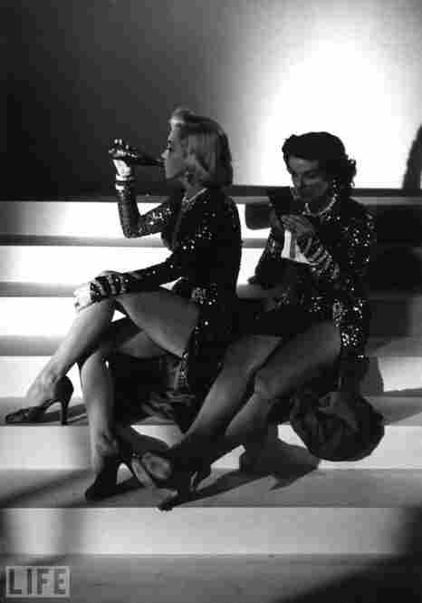 During a break on the set of Gentleman Prefer Blondes, photographer Ed Clark catches Marilyn Monroe drinking a Coke and Jane Russell fixing her makeup.