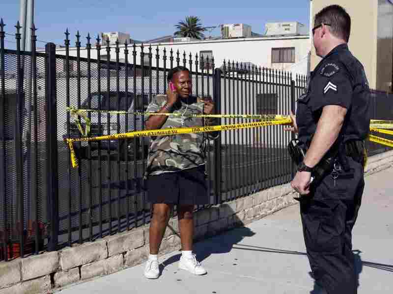 A resident talks with a Los Angeles police officer after another officer was wounded during a shooting in the city in August. Under a program the LAPD is rolling out this month, computer statistics will be used to predict where a crime will occur. Officials hope that the technique will help reduce crime.
