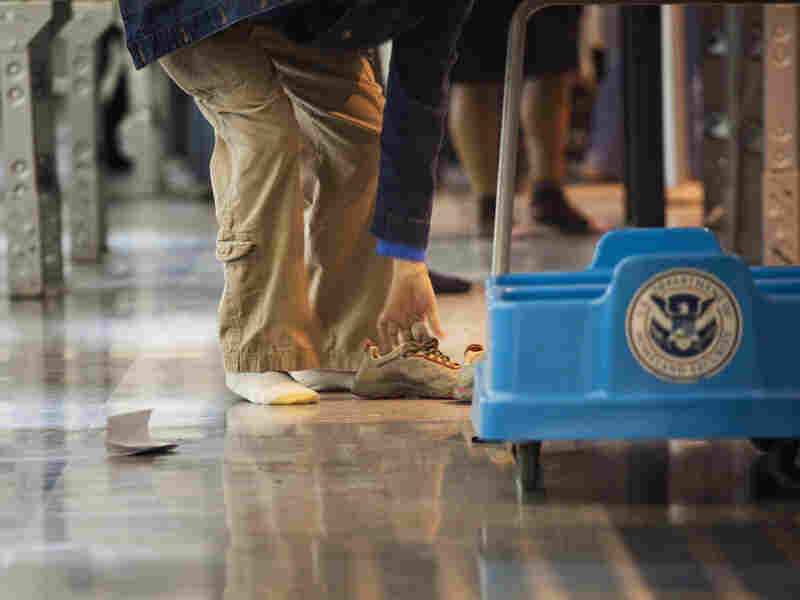 A passenger removes his shoes at the TSA security checkpoint at John F. Kennedy International Airport — a task that may not be required in the near future, says Department of Homeland Security Secretary Janet Napolitano.