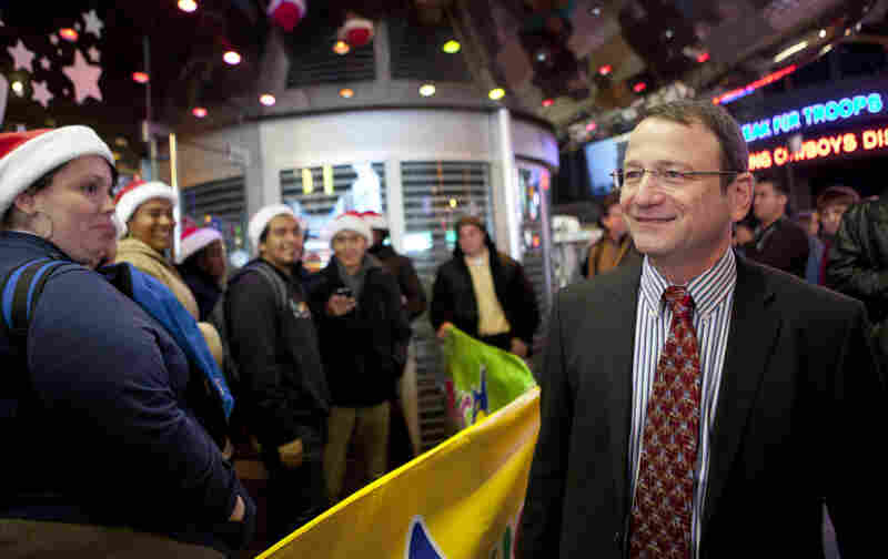 Gerald L. Storch, CEO and chairman of Toys R Us, speaks with customers waiting in line outside the company's store in Times Square in New York on Thanksgiving.