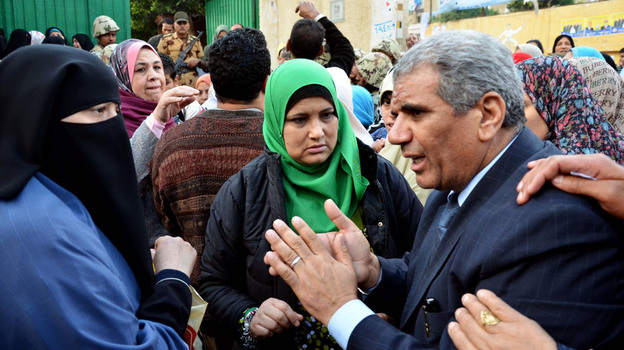 Sobhi Saleh, right, a senior member of the Muslim Brotherhood and candidate for parliament, speaks to voters at a polling station in Alexandria, Egypt on Monday. The Brotherhood is expected to make a strong showing in the polls.