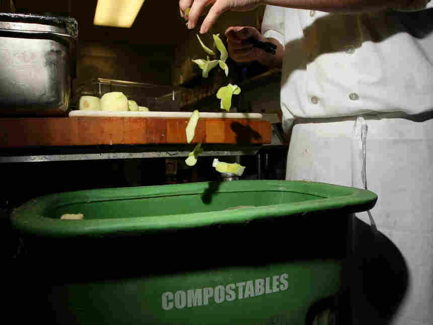A prep cook drops apple skins into a food scrap recycling container in San Francisco.