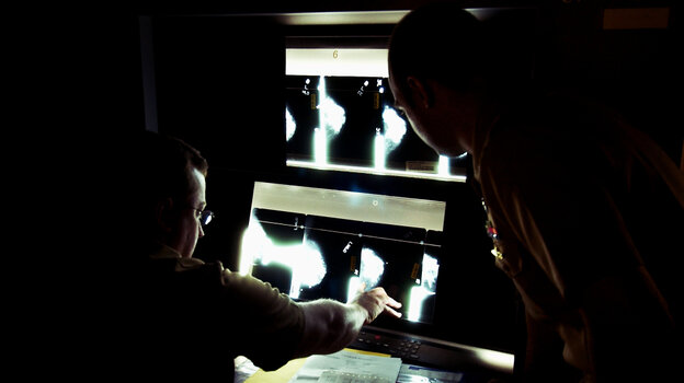 U.S. Navy doctors Lt. Cmdr Ralph Pickard (left) and Ens. Jesse Rohloff study a patient's mammogram images at the National Naval Medical Center in Bethesda, Md.