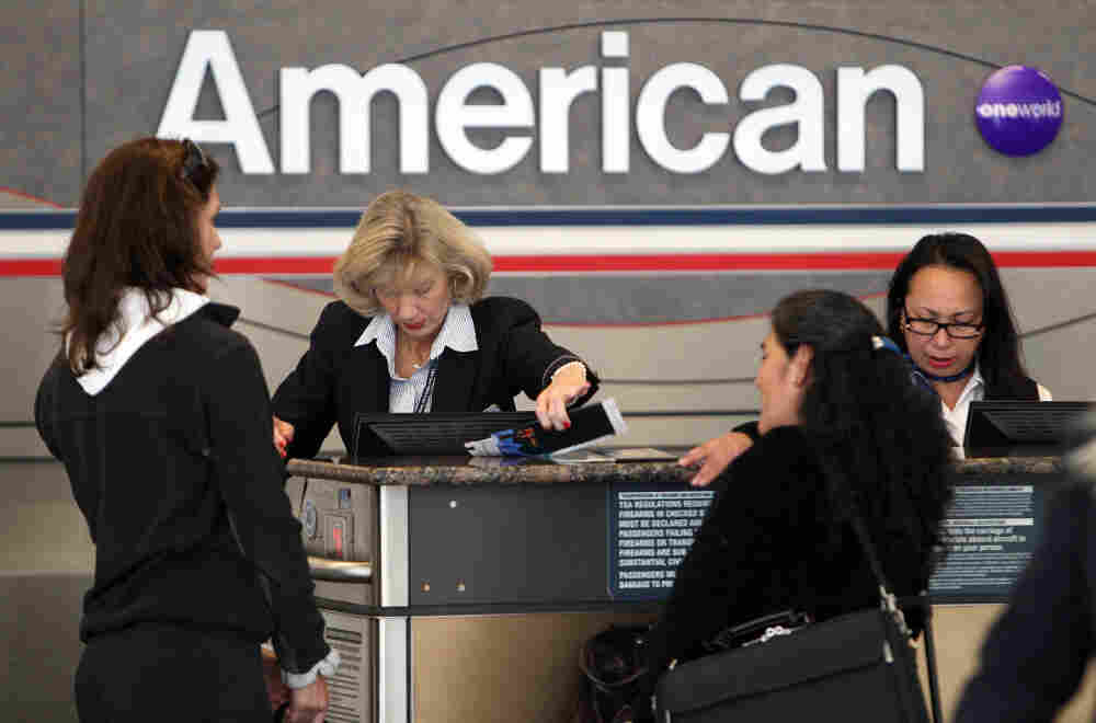 Passengers check in at an American Airlines ticketing counter at Dallas/Fort Worth Airport on Tuesday. American's parent company, AMR, filed for Chapter 11 bankruptcy protection as it seeks to cut costs and unload massive debt.