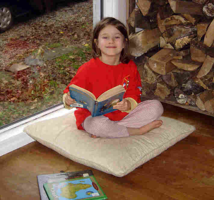 Lucia Kasper, 6, sits in her favorite reading spot at her home in Hiram, Ohio. In the past few weeks, she has read The Phantom Tollbooth three times.