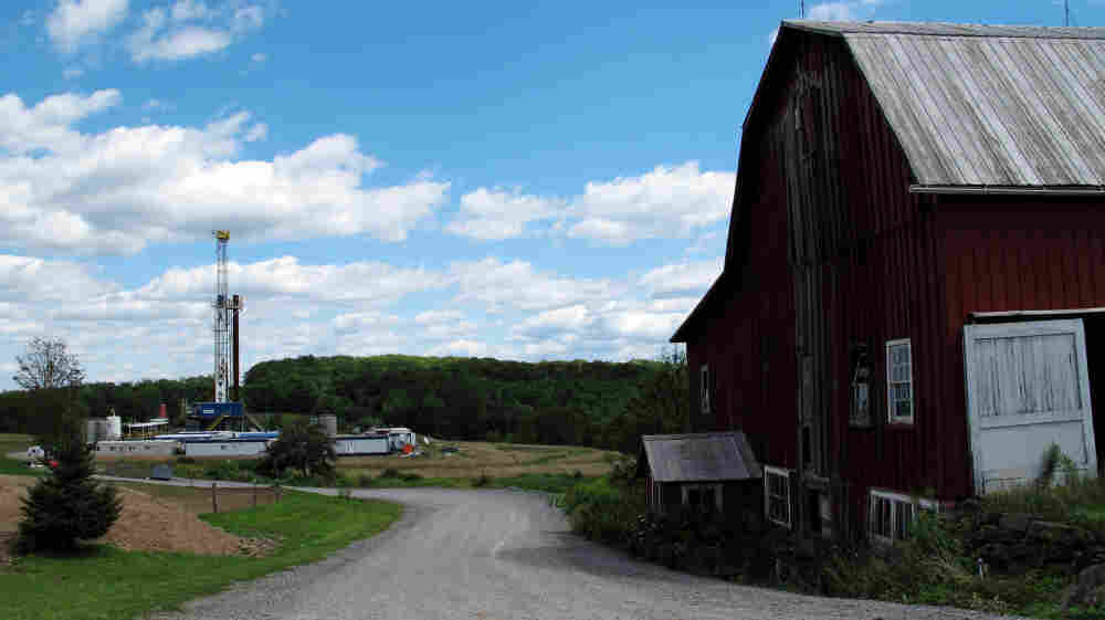 A drilling rig looms behind a barn in Tioga County, Pa.