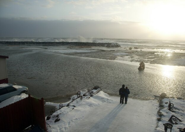 In this Nov. 9 file photo, a couple stands in front of River Street while the waves hit the seawall, in Nome, Alaska.