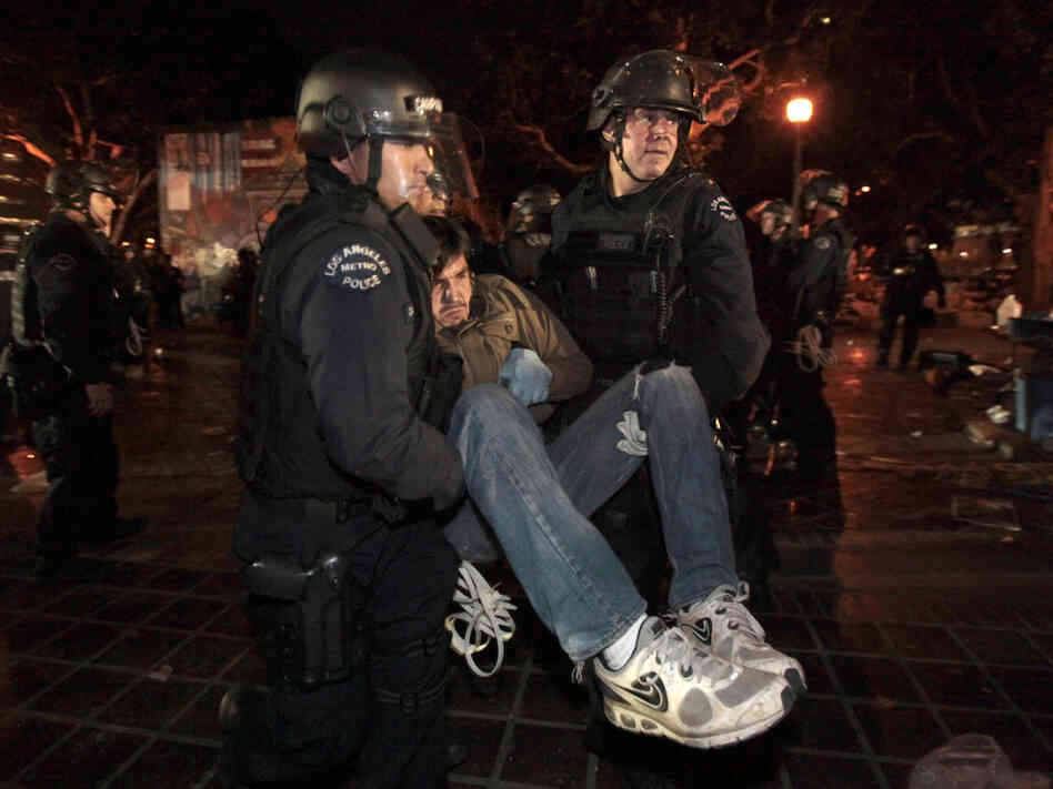 An Occupy protester is arrested early today in Los Angeles as authorities cleared the site near city hall that had been occupied for two months.