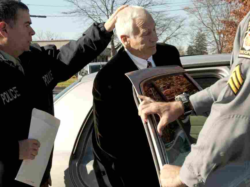 Jerry Sandusky, center, is placed in a police car in Bellefonte, Pa. on Saturday, Nov. 5.