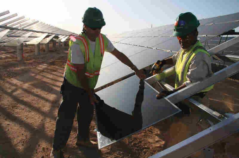 Workers install solar panels at the Soaring Heights Communities at Davis-Monthan Air Force Base outside Tucson, Ariz.
