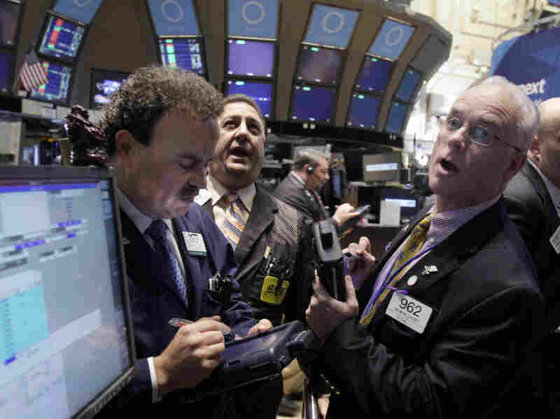 Traders work on the floor of the New York Stock Exchange Wednesday. Stocks soared on news that central banks agreed to work together to support the global financial system.