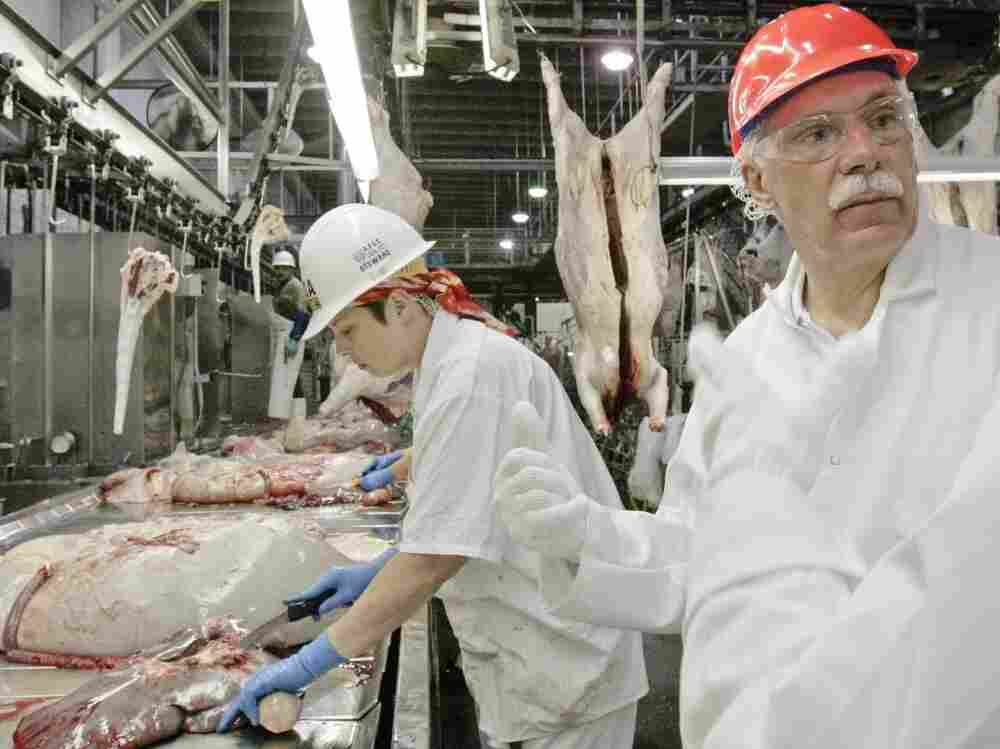 Former Agriculture Secretary Ed Schafer, right, follows the work of USDA inspectors at a Cargill meat packing plant in Schuyler, Neb., in 2008.