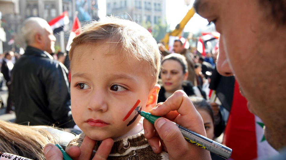 A supporter of Syria's government draws the Syrian flag on a child's face during a pro-regime rally in Damascus on Friday.
