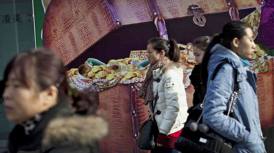 Chinese women walk past a billboard showing a box full of gold coins and jewelry, outside a shopping mall in Beijing on Thursday. Chinese leaders are scrambling to shore up flagging economic growth as exports weaken, abruptly reversing course after th