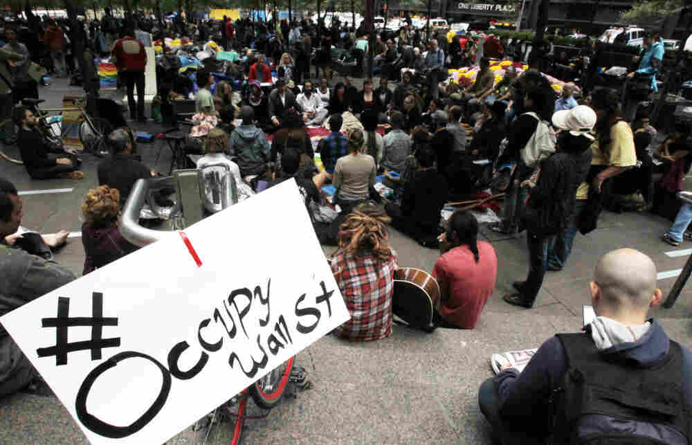 Occupy Wall Street protesters meditate while a sign bearing their Twitter hashtag hangs from a railing in Zuccotti Park in October. Some activists accused Twitter of censorship because #OccupyWallStreet wasn't appearing on trending lists.