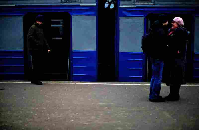 Passengers wait for a local train at a small station.
