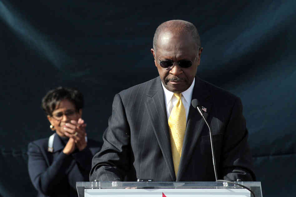 With his wife, Gloria, standing behind him, Herman Cain announces that he is suspending his run for the GOP presidential nomination, outside his campaign headquarters in Atlanta on Dec. 3.