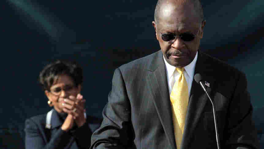 With his wife, Gloria, standing behind him, Herman Cain announces that he is suspending his presidential campaign, outside his campaign headquarters in Atlanta on Saturday.