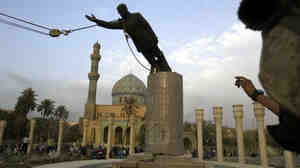 A U.S. marine watches a statue of Saddam Hussein being toppled in Firdaus Square, in downtown Baghdad, on April 9, 2003.