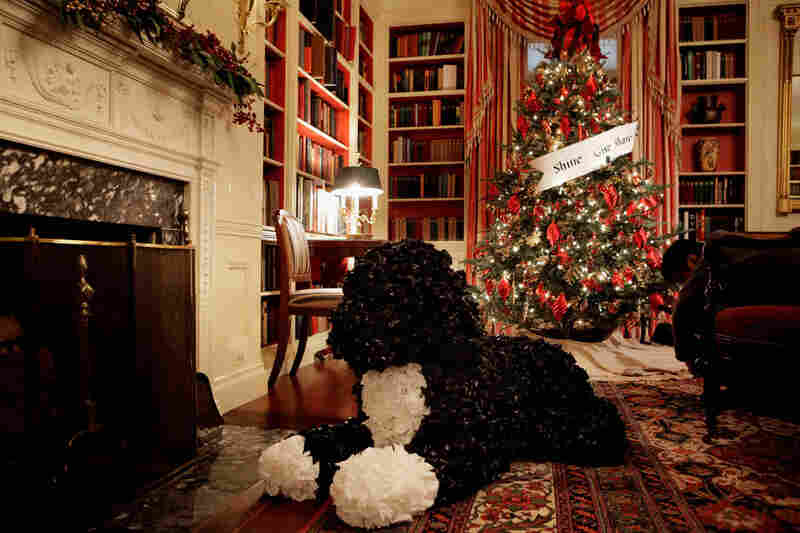 "A ""Bo"" made from plastic garbage bags sits in front of the fireplace in the library. Mrs. Obama drew a laugh from the crowd when she said Bo, ""the most famous member of the Obama family,"" has been a little confused walking around the house and seeing himself in ""gigantic form."""