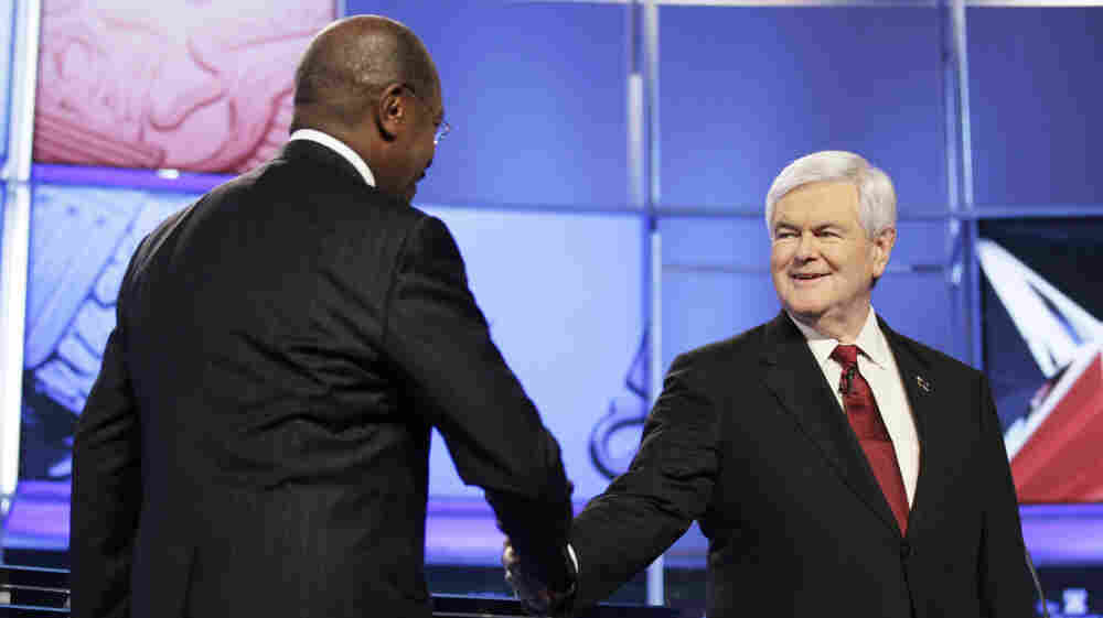 Herman Cain, who has since suspended his presidential campaign, greets Newt Gingrich upon arriving at CNN's GOP National Security debate in Washington on Nov. 22.