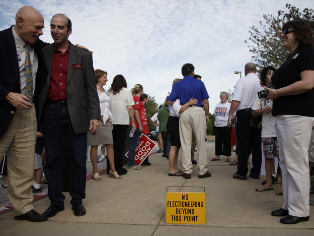 Former Maryland Gov. Bob Ehrlich (center, in the blue shirt) greets voters outside a polling place in Ellicott City, Md., in 2010. Ehrlich campaign manager Paul Schurick is now facing charges for allegedly discouraging voters from going to the polls on Election Day.