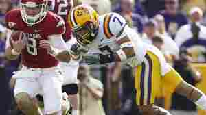 "LSU cornerback Tyrann Mathieu (right) earned the nickname ""Honey Badger"" for hits like this one, against Arkansas quarterback Tyler Wilson on Nov. 25, 2011. Mathieu is one of five finalists named Monday for the Heisman Trophy."
