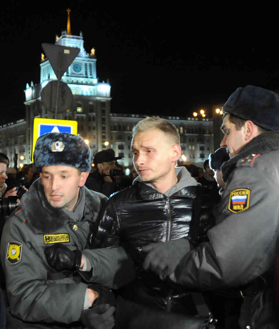 Police officers detain an opposition activist during an unauthorized rally in central Moscow, Tuesday.