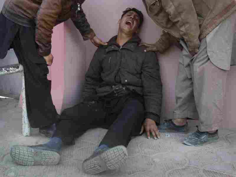 Relatives comfort an Afghan man outside a Kabul hospital where victims of Tuesday's suicide bombing were taken. A suicide bomber struck a crowd of Shiite worshippers marking a holy day in the Afghan capital.