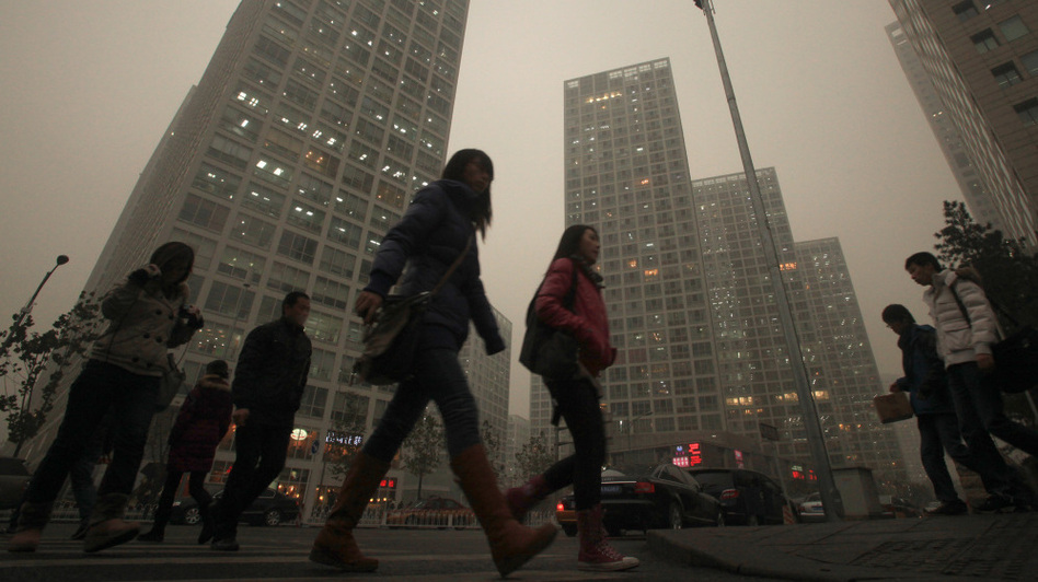 Chinese walk to work midday as heavy smog hangs over downtown Beijing. (UPI /Landov)