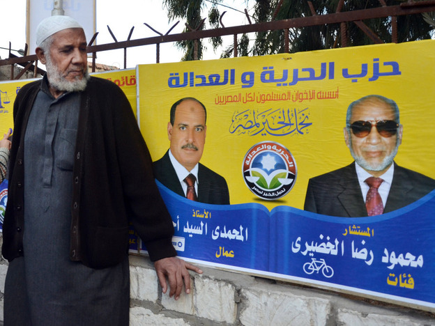 An Egyptian man in front of a campaign banner for the Muslim Brotherhood's Freedom and Justice Party, during the recent parliamentary voting in Alexandria, Egypt. (AP)