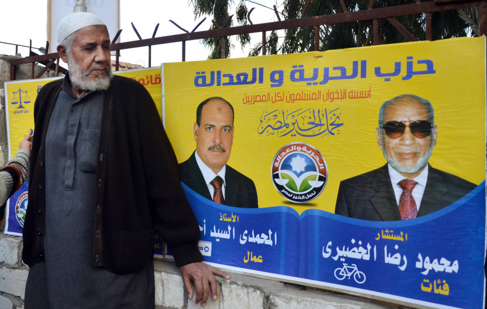 An Egyptian man in front of a campaign banner for the Muslim Brotherhood's Freedom and Justice Party, during the recent parliamentary voting in Alexandria, Egypt.