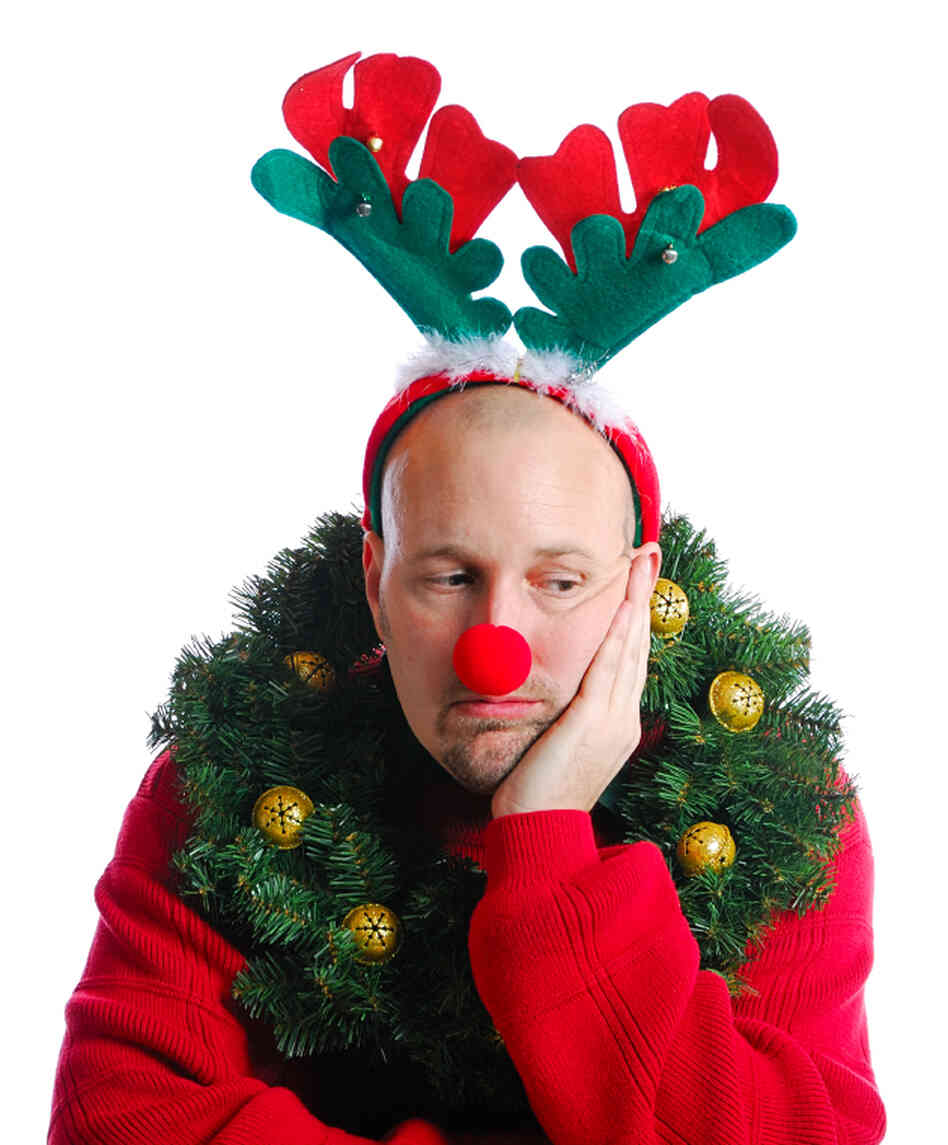 A man bedecked in Christmas attire and looking miserable.