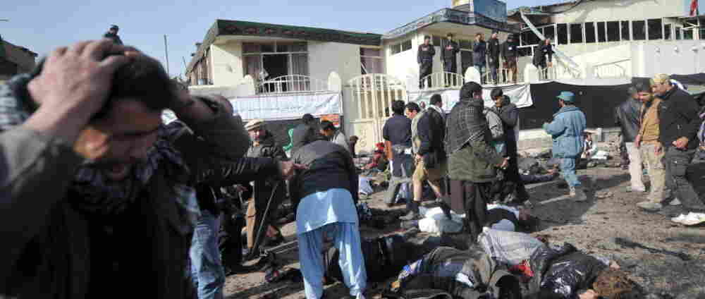 A man grieves as others try to help victims and remove bodies from the scene in Kabul earlier today (Dec. 6, 2011) after a suicide bomb exploded in a crowd of Shiite worshipers.