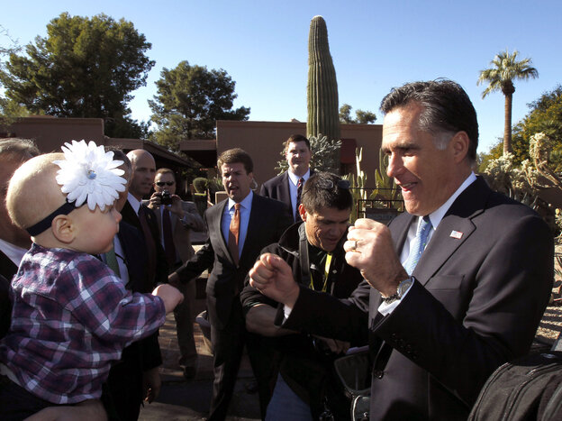 Mitt Romney entertains a toddler in Paradise Valley, AZ, Tuesday, Dec. 6, 2011.