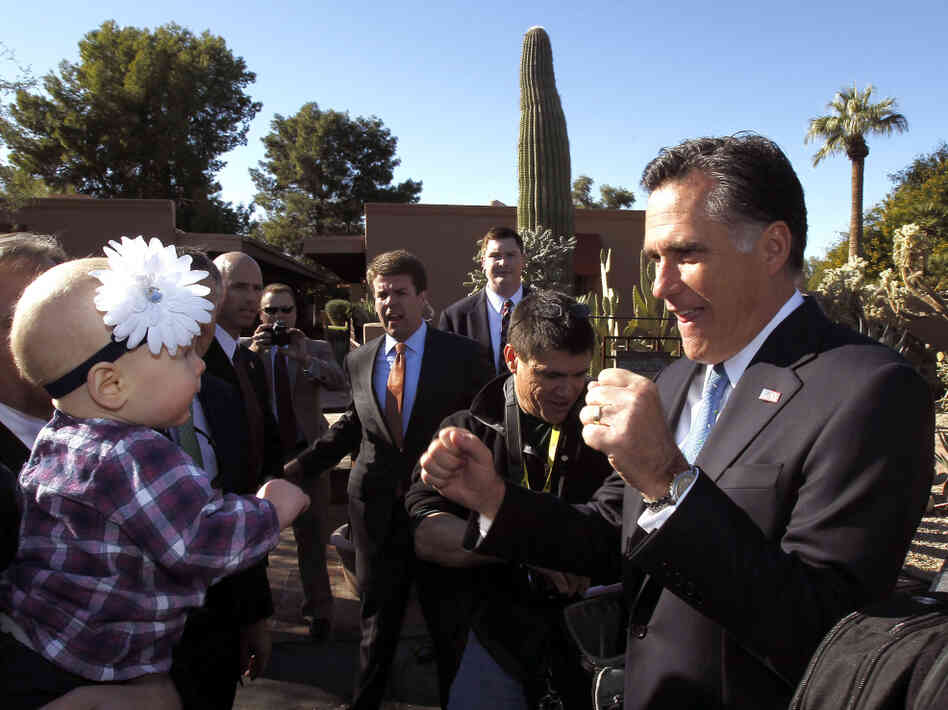 Mitt Romney entertains a toddler in Paradise Valley, AZ, Tuesday, Dec. 6, 2011.