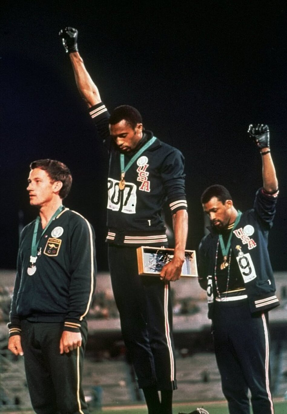 """In this Oct. 16, 1968 photo, extending gloved hands skyward, U.S. athletes Tommie Smith (center) and John Carlos (right) stare downward during the playing of the """"Star-Spangled Banner"""" at the Summer Olympic Games in Mexico City."""