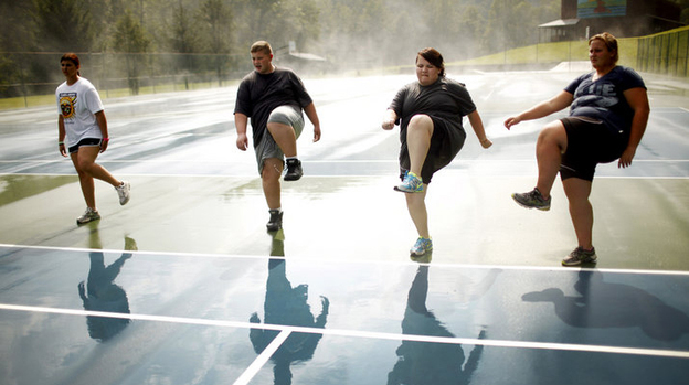 Wellspring students do high steps on the tennis court. Exercise is paramount at Wellspring, and a little rain doesn't get in the way of outdoor activities. (Travis Dove for NPR)