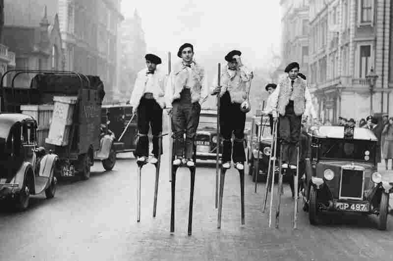 French stilt dancers from Landes, in southwestern France, walk through London on their way to the 1937 Silver Jubilee Festival of the English Folk Dance and Song Society.