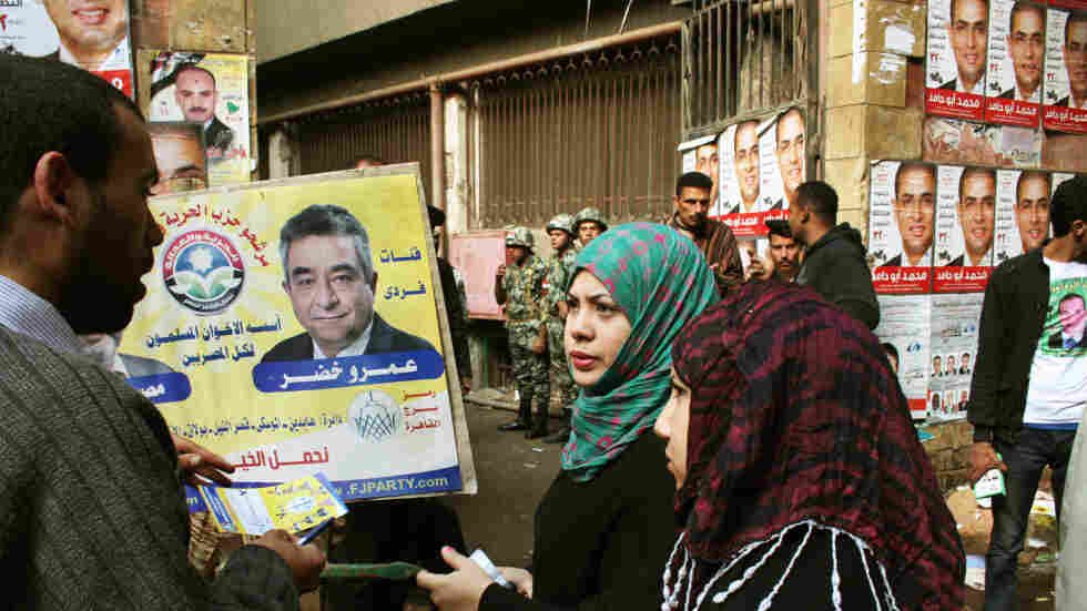A campaigner for the Muslim Brotherhood's Freedom and Justice Party talks to voters in front of a polling station in Cairo on Nov. 28.