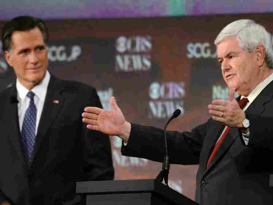 Mitt Romney watches as Newt Gingrich talks during Republican presidential debate in Spartanburg, S.C.