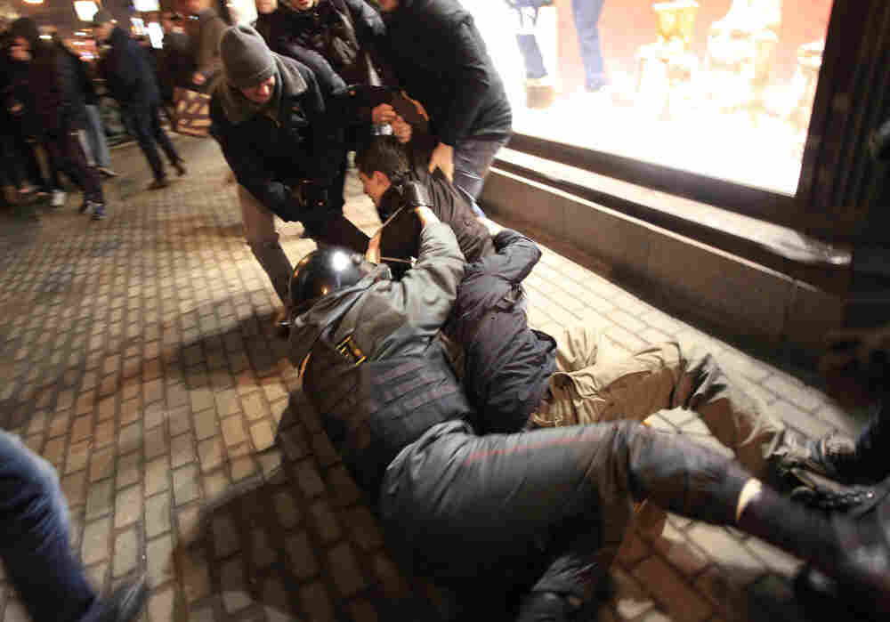 A police officer, center, falls down as he tries to detain a demonstrator during protests against alleged vote rigging in Russia's parliamentary elections in Triumphal Square in Moscow.