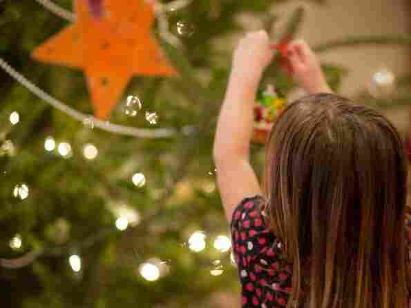 A child decorates a Christmas tree